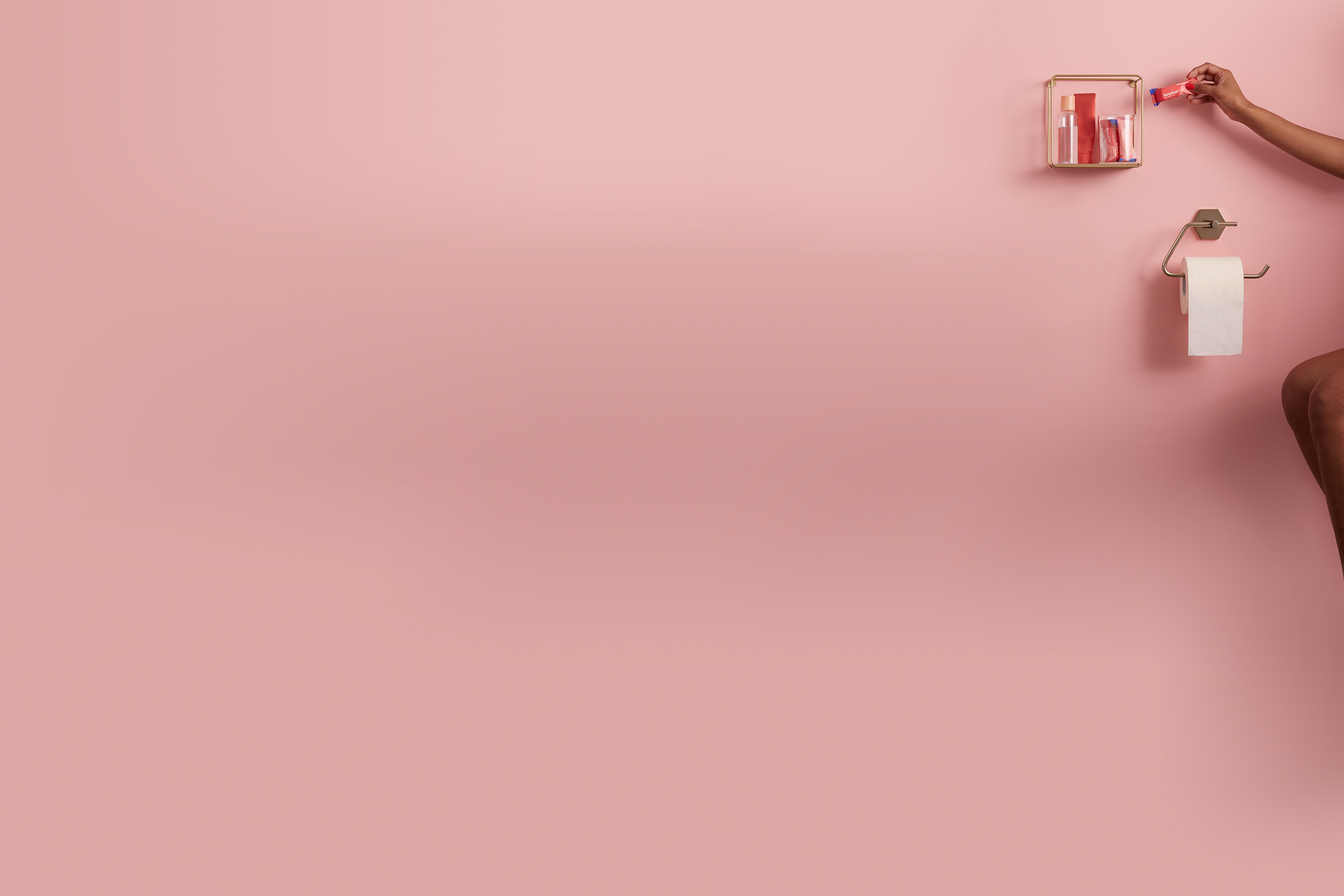 An arm reaches into a pink bathroom to remove a Callaly organic tampliner from a wooden shelf