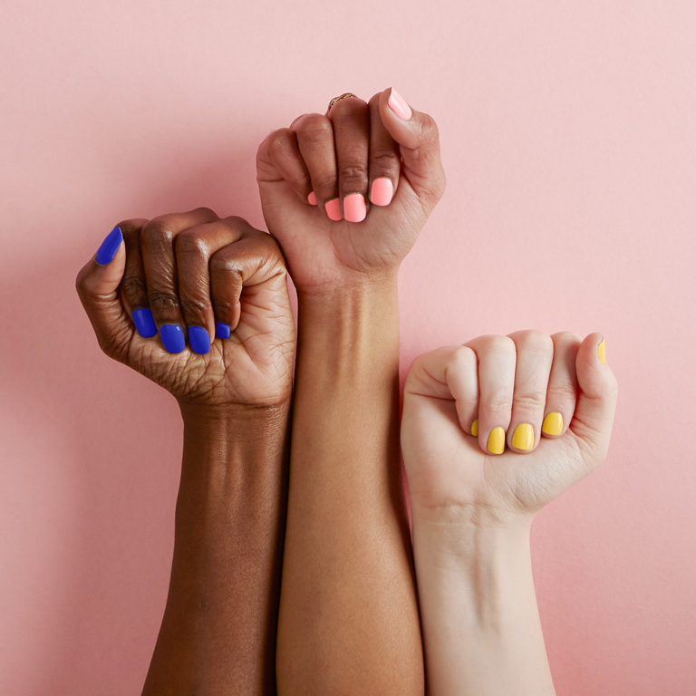 Three hands in different skin tones with multicoloured nail varnish form fists of protest in solidarity