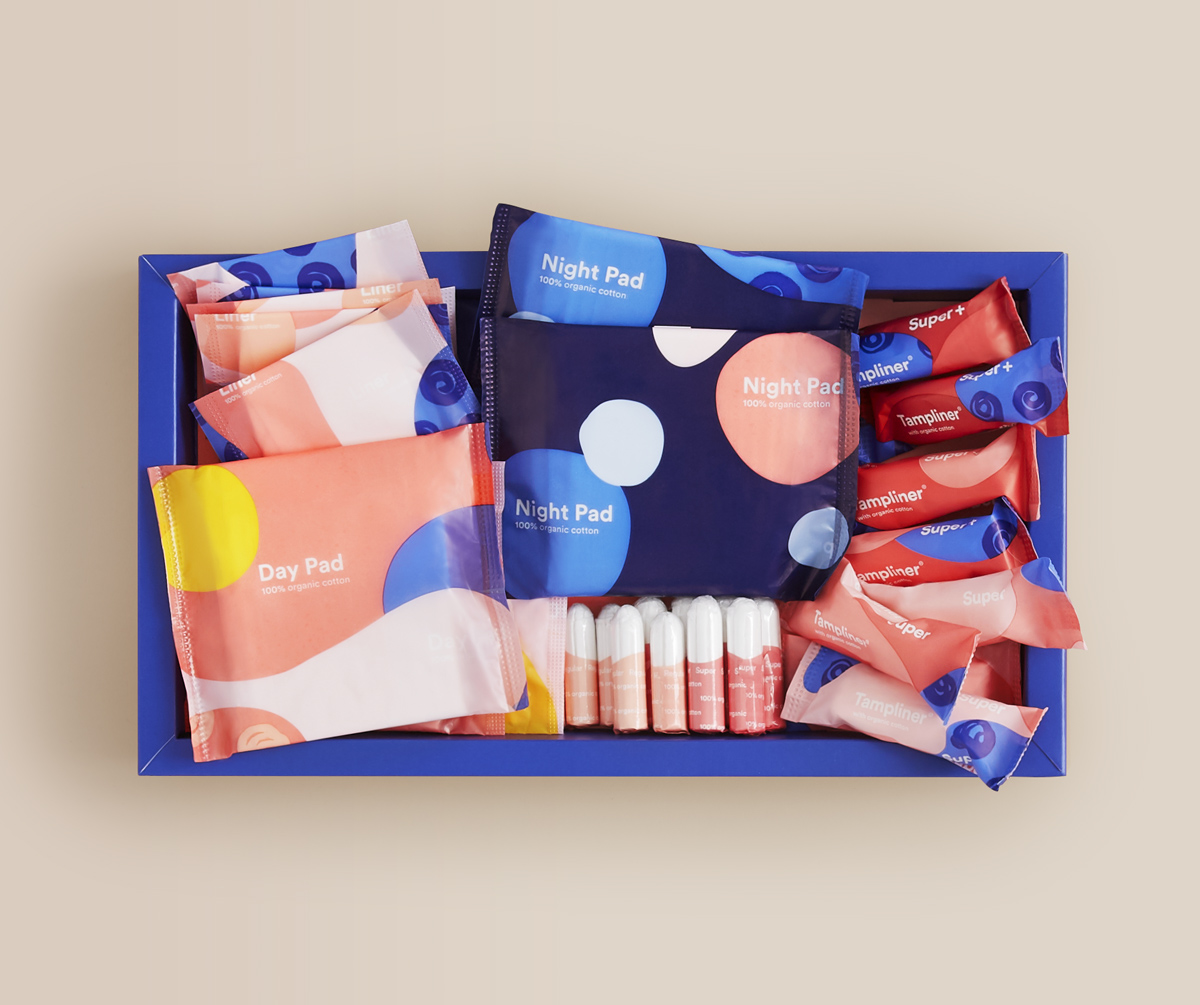 A large open Callaly box containing organic pads, liners, tampons and tampliners lies on a plain surface
