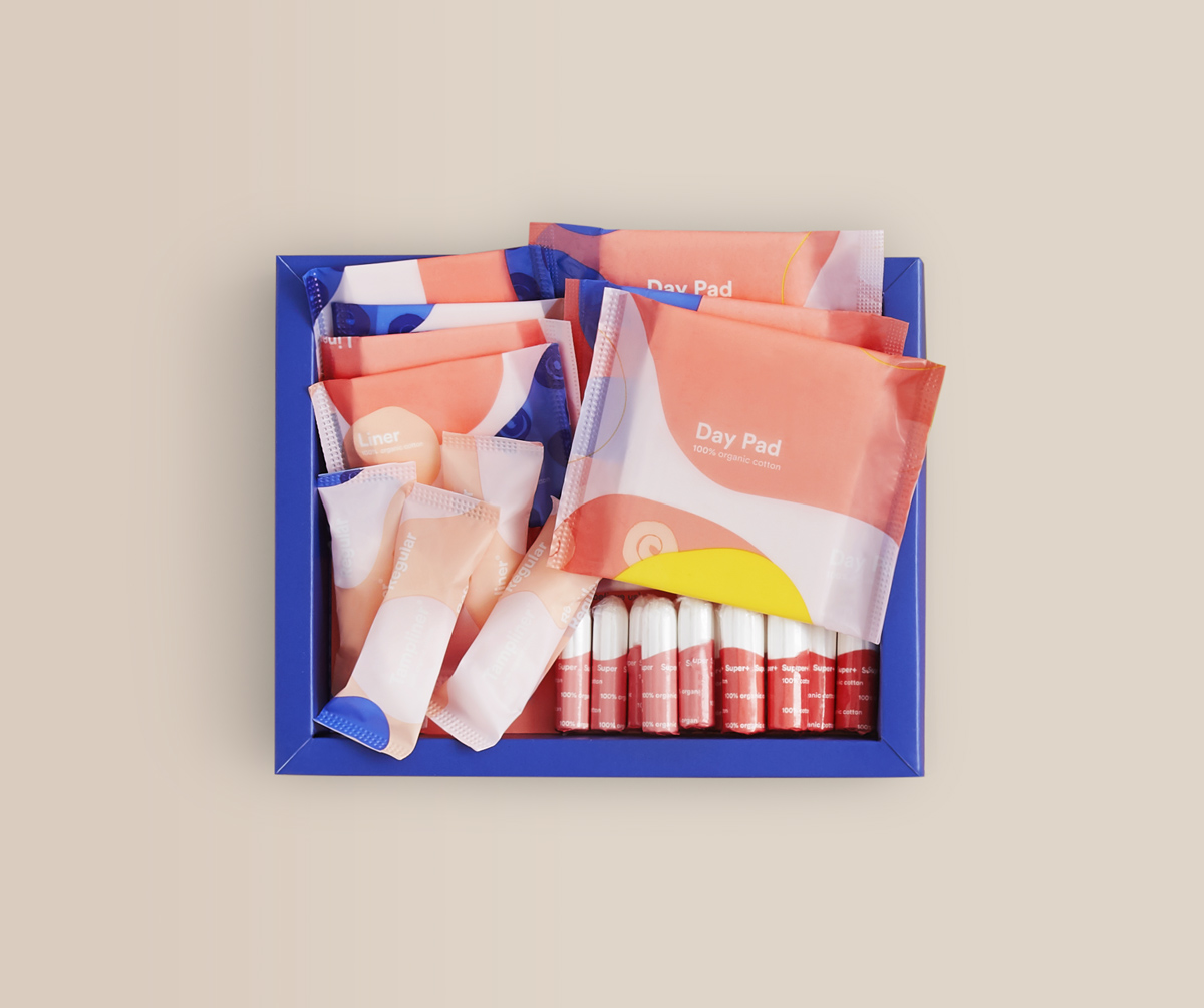 A medium open Callaly box containing organic pads, liners, tampons and tampliners lies on a plain surface