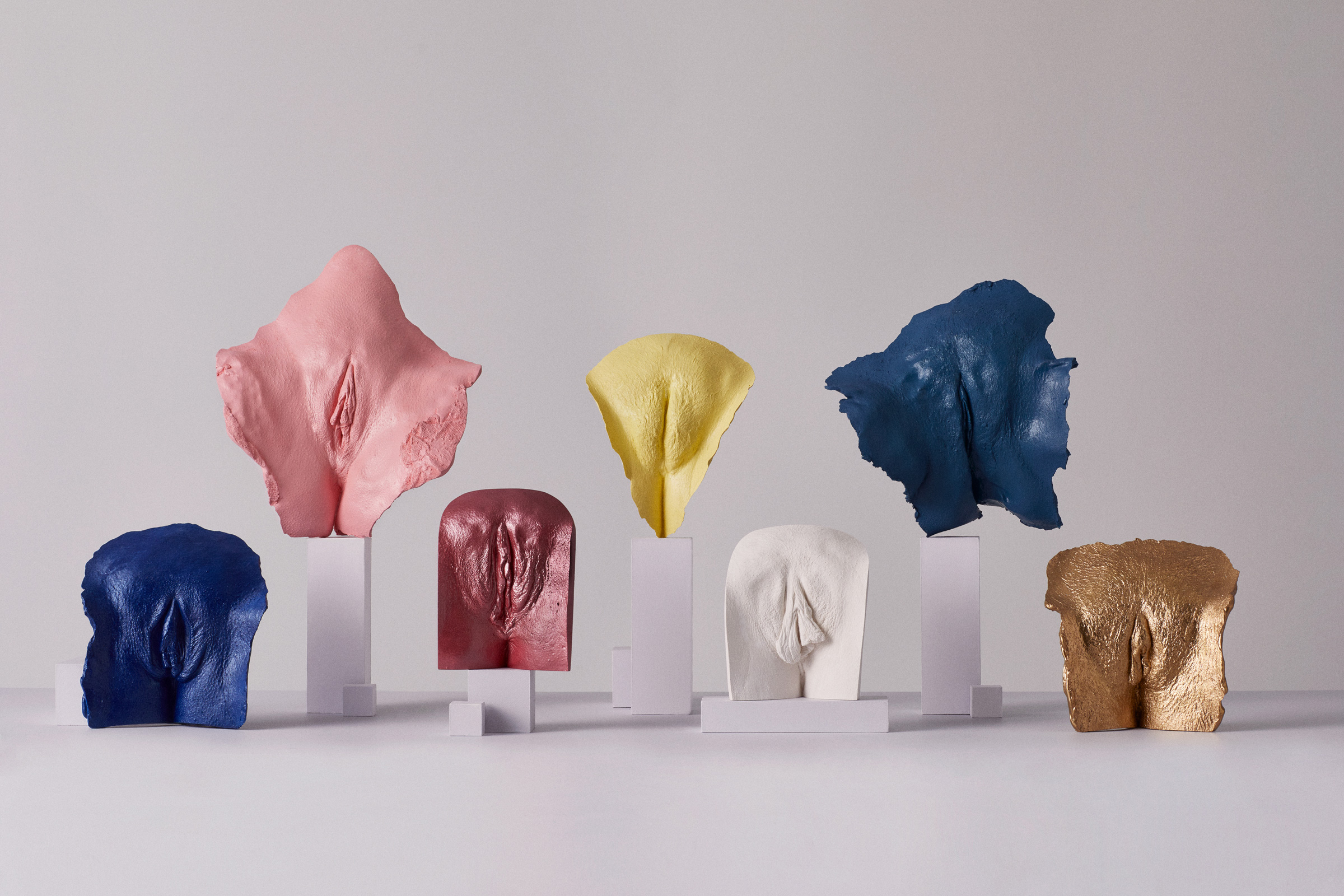 Several casts of different vulvas stand around on plinths, showcasing the natural variety of vulvas