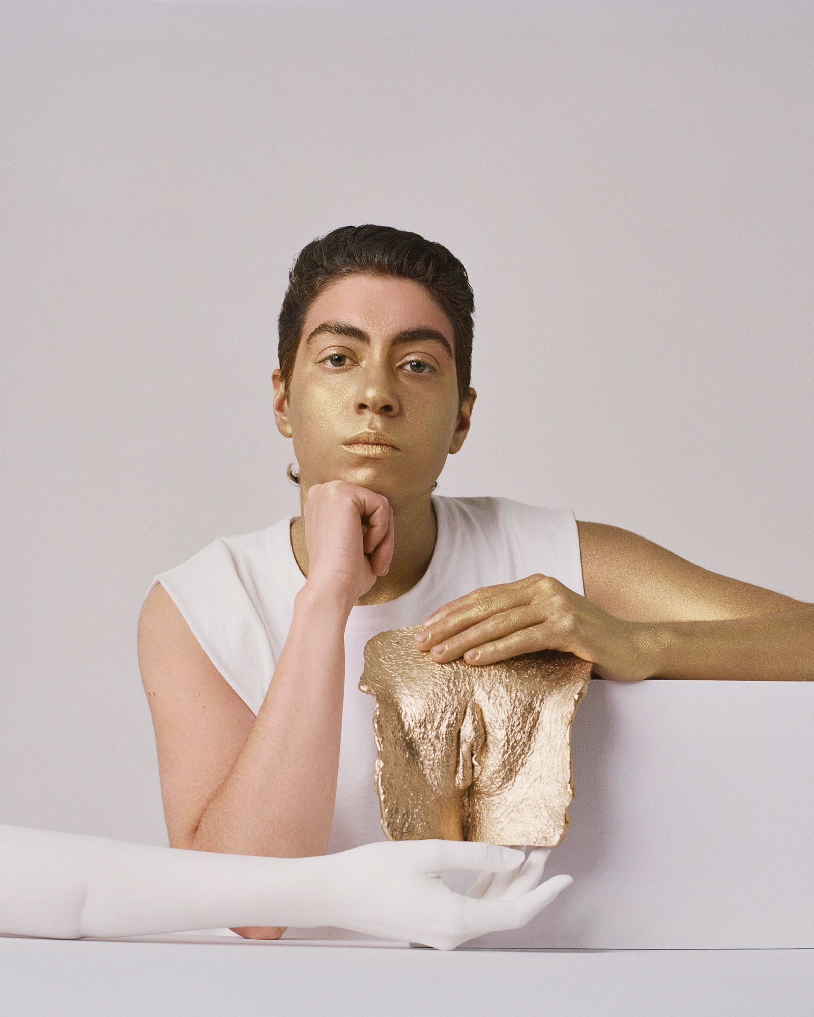 Vic sits with a cast of his vulva, staring into the camera. His left hand is painted                             gold to                             match the cast it rests on.
